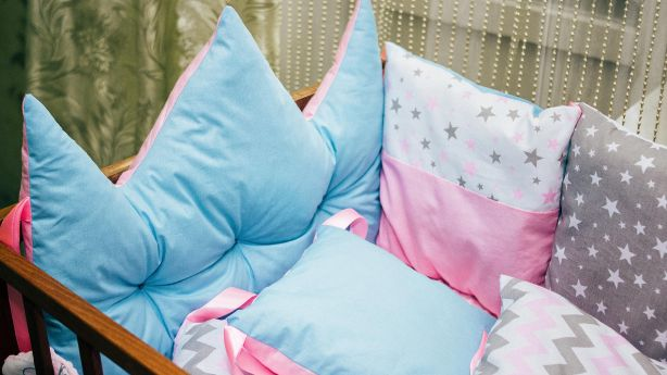 Cots and pillows and bumpers of different colors. Turquoise pillow, crown, grey, pink and turquoise pillows with geometric patterns.